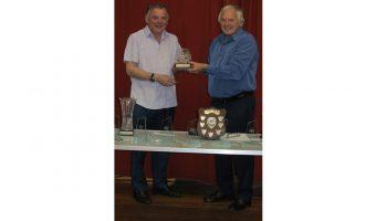 David receiving his trophy from Geoff